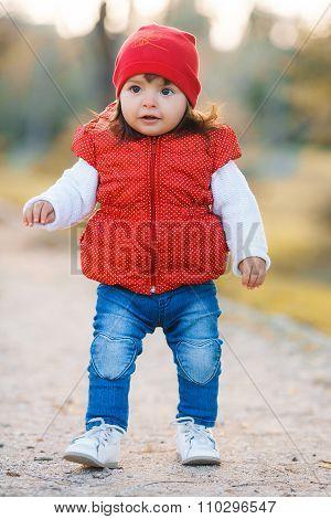 Little girl in yellow autumn park