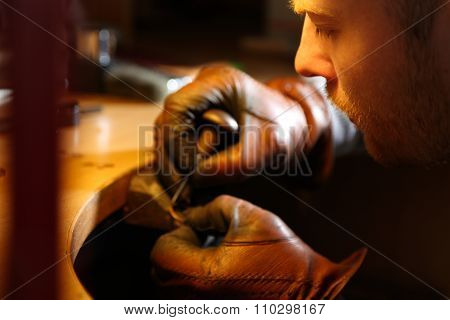 Jeweler engraving the ring with sharp awl