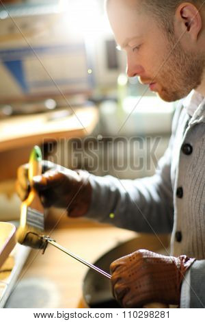 Jeweler brushes his tool