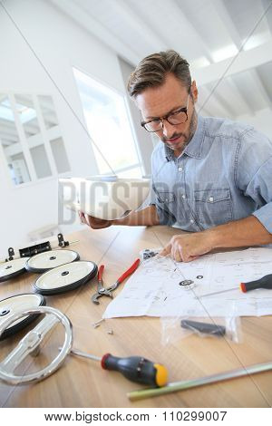 Man at home assembling toy car parts