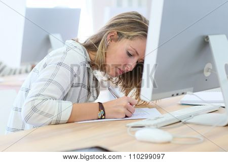 Student girl writing an exam in computers' room
