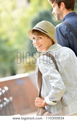 Happy young woman walking in park, holding boyfriend's hand