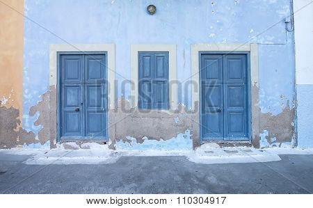Mediterranean style exterior. Blue wooden doors and window shutters, old painted wall on a Greek isl