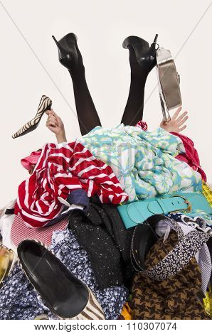Woman Legs And Hands Reaching Out From A Big Pile Of Clothes And Accessories.