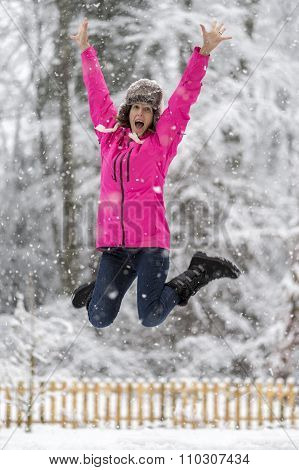 Happy Cheerful Young Woman Jumping High Up In The Air Lifting Her Arms High