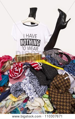 Woman Legs Reaching Out From A Big Pile Of Clothes With A T-shirt Saying Nothing To Wear.