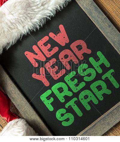 New Year Fresh Start written on blackboard with santa hat