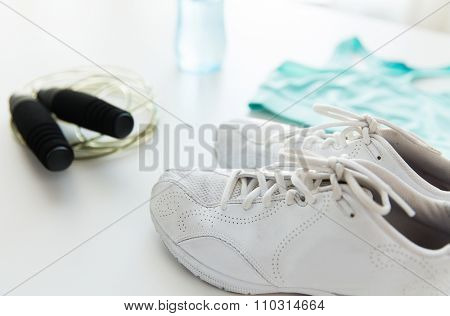 sport, fitness, healthy lifestyle, cardio training and objects concept - close up of female sports clothing, skipping rope and bottle set
