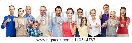 gesture, sale and people concept - group of smiling men, women and kids showing thumbs up and holding shopping bags with money