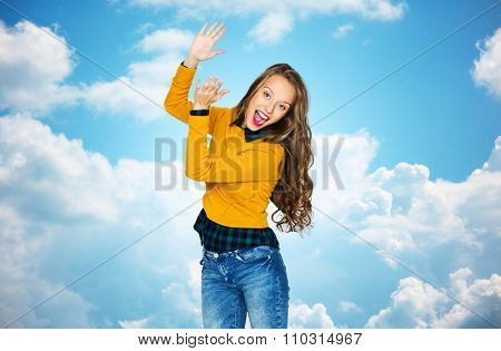 people, style and fashion concept - happy young woman or teen girl in casual clothes having fun and applauding over blue sky and clouds background