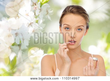 beauty, people and lip care concept - young woman applying lip balm to her lips over green natural background with cherry blossoms