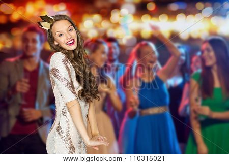 people, holidays, nightlife and celebration concept - happy young woman or teen girl in party dress and princess crown at night club party over crowd and lights background