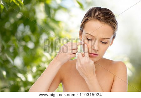beauty, people, skincare and health concept - young woman squeezing pimple on her face over green natural background