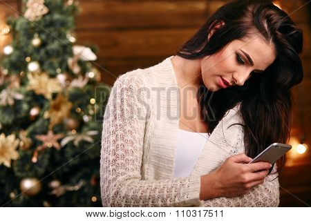 Young pretty woman with mobile phone chatting typing sms near christmas  tree