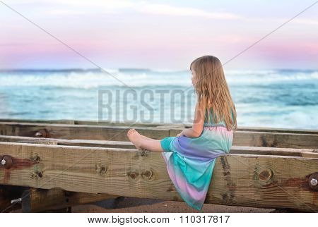 little girl sitting on a bench on a beach and looking at the ocean