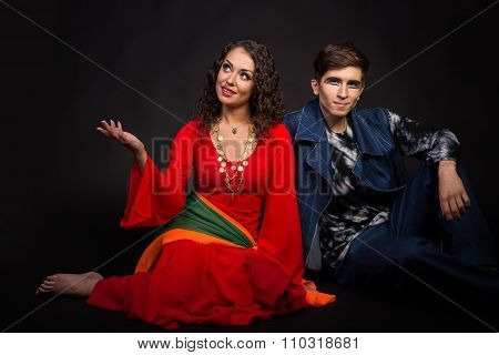 Two actors posing on a dark background.
