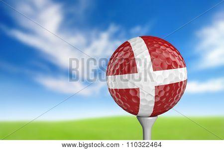 Golf ball with Denmark flag colors sitting on a tee