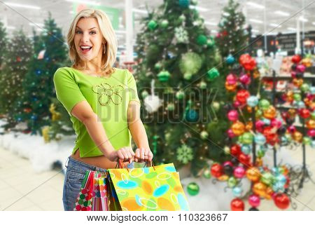 Happy Christmas girl with gift over Xmas tree background.