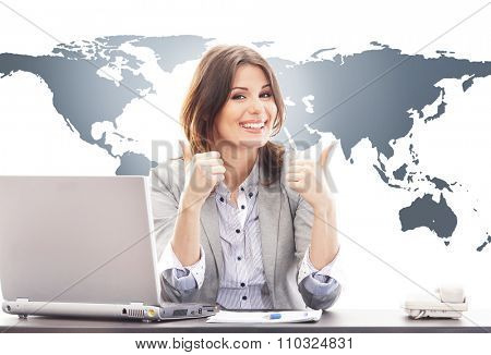 Beautiful business woman with thumbs up in office on world map background. Global business concept.