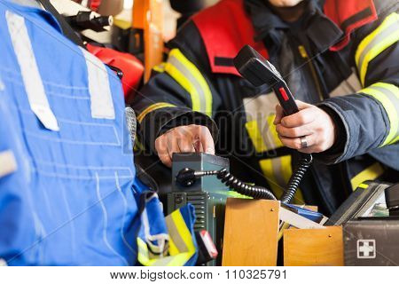 firefighter uses a radio device in the emergency vehicle