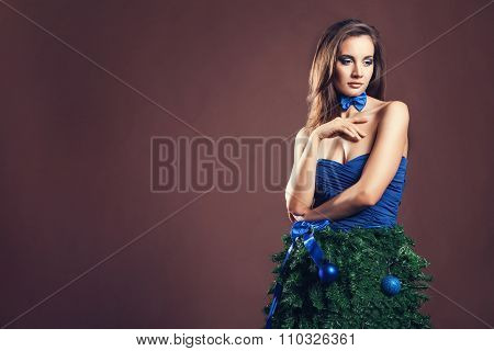 Sensual Woman In Christmas Tree Dress On Brown Background