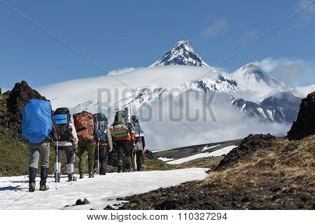 Group Of Hikers Goes In Mountain On Background Volcanos