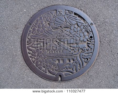 Manhole drain cover on the street at Osaka, Japan.