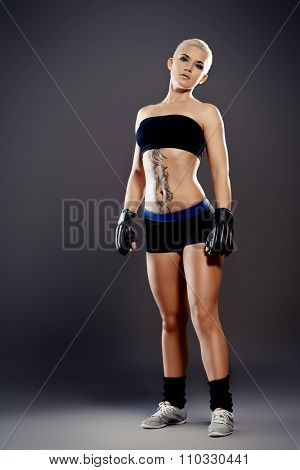 Portrait of a professional athlete woman bodybuilder with a perfect athletic physique. Fitness sports. Healthcare, bodycare. Martial arts, fighter.