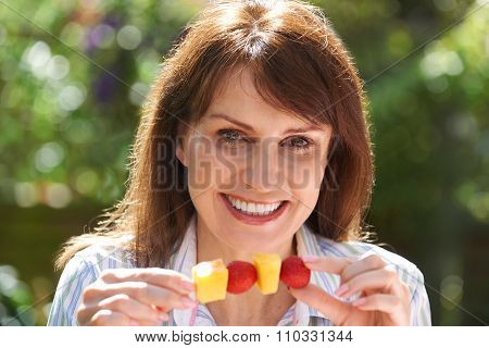 Middle Aged Woman Eating Fruit Kebab In Garden