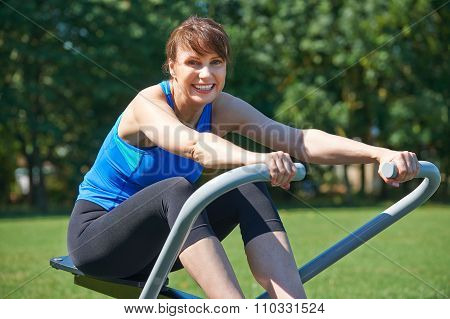 Middle Aged Woman Exercicing On Rowing Machine In Park
