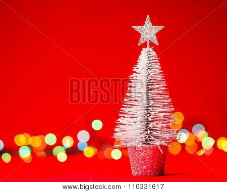 Small tabletop Christmas tree with blurred christmas lights in background
