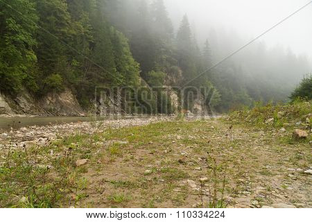 Beautiful rocky mountain landscape. Stones and boulders strewn shore of a mountain river.