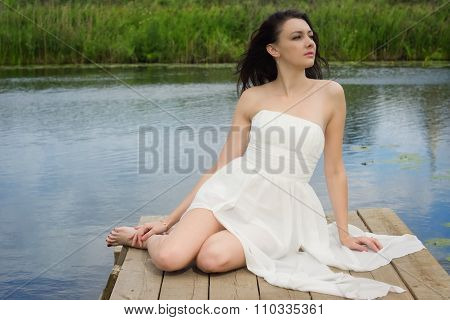 Relaxing Young Woman On Wooden Pier At The Lake