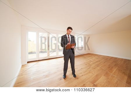 Estate Agent Looking At Vacant Property