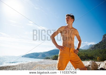 Man standing at sunrise on the water