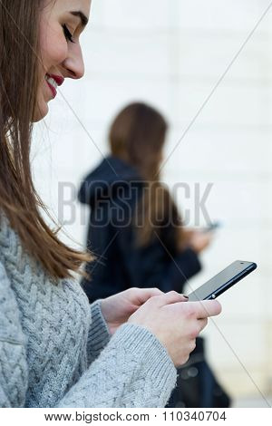 Two Young Businesswoman Using Mobile Phone In The Street.