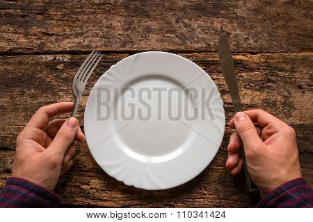 Man Holding A Knife And Fork Next To The Plate On A Wooden Background
