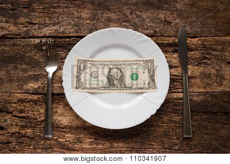 One Dollar On A White Plate Next To Fork And Knife