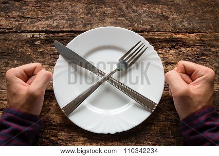 Man Refuses To Eat Spoon And Fork On A Plate Stacked In The Shape Of A Cross