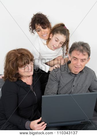 Senior People With Daughter And Grand Daughter Doing Shopping Online