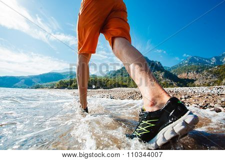 Man running at sunrise on the water