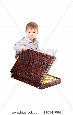 The child is sitting with a suitcase full of gold ingots