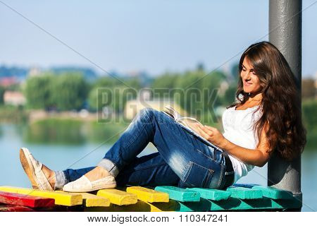 a girl sits on a bench and reads a book