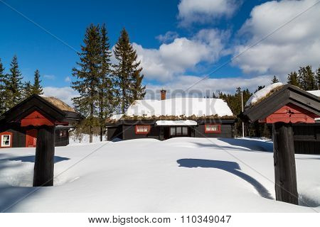Traditional Norwegian Cabin Surrounded By Deep Snow With Two Pillars