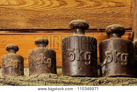 The Old Calibration Weights In A Shed At Wooden Wall