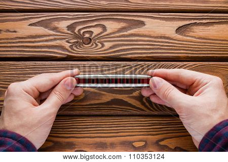 Man Holding A Harmonica On A Wooden Background