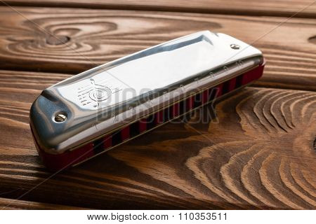 Harmonica On Wooden Background Closeup