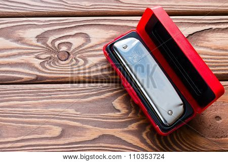 Harmonica In A Red Box On A Wooden Background