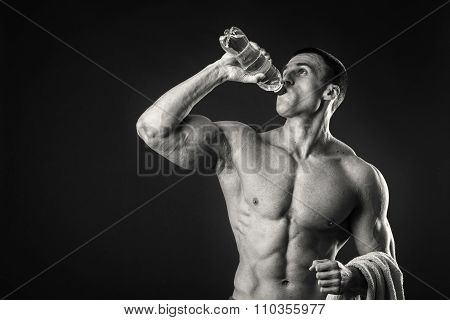 Man bodybuilder posing on gray background Man is holding a shaker for drinks.