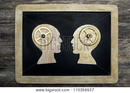 Two human head silhouettes with gears